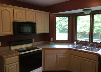 cream-kitchen-cabinets-with-deep-red-walls