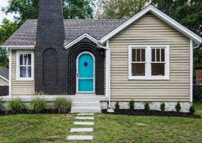 black-brick-chimney-and-home-exterior-with-bright-blue-accent-door